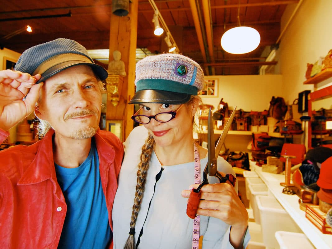 Man and woman standing in a hat shop with the woman holding scissors up