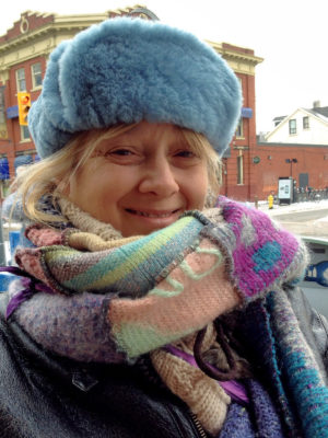 A close up of a happy customer wearing her new light blue Winter Wave hat on a woman outside