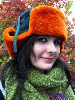 A close up of a orange and green Winter Wave hat on a woman outside in the Fall.