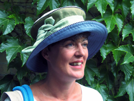 A close up of a woman wearing her new blue and green Zinnia summer hat.
