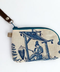 image of a small woman's person fishing under a shelter blue toile linen zipper card wallet on its one side
