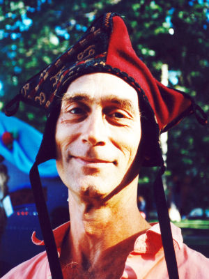 Close up of man smiling wearing a red Four Corner Hat.