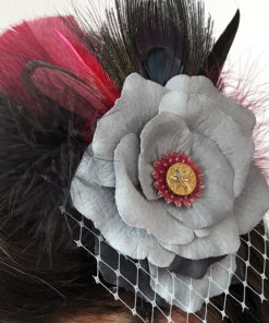 A close up of the grey rose hair clip fascinator in a woman's hair