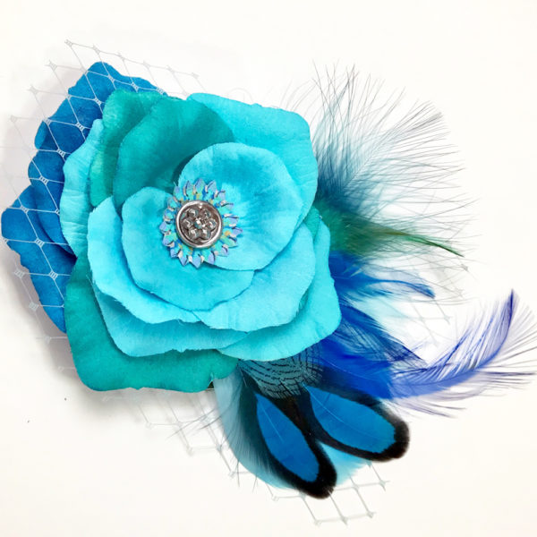 Close up of Turquoise Blue Rose Fascinator on white background