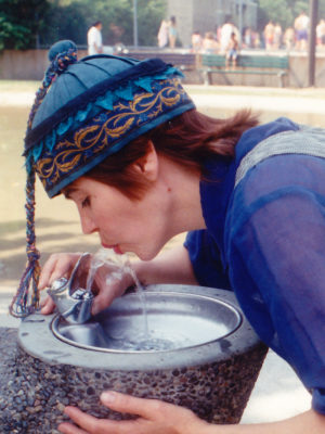 Close of Gwendolyne drinking from a fountain of water wearing a blue silk cap.