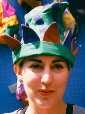 Close up of a woman wearing a green and red Petal hat