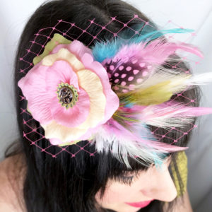Close up of woman wearing a Pink Ivory White Turquoise rose hair-clip fascinator in her hair