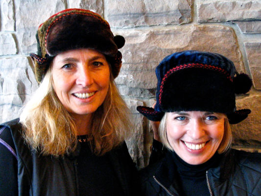 Close up of 2 women wearing a brown and blue Pom Pom hats