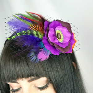 Close up of woman wearing a purple rose hair clip fascinator in her hair