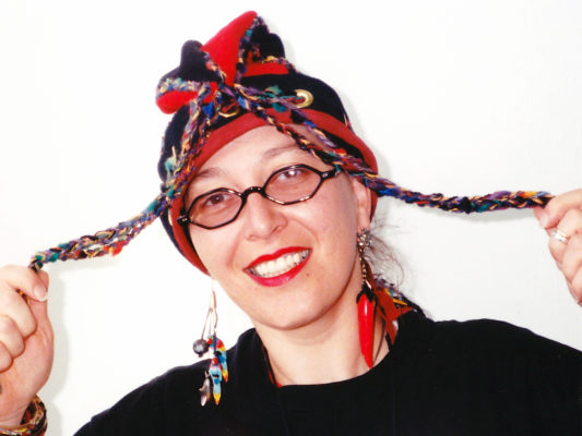 Close up of woman wearing a red and black Squid Toque with long tassels.