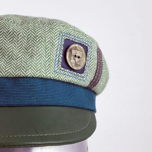 Close view of the leather peak and vintage button on the mint green Abbey Road cap against a white background