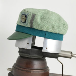 Side view of a mint green Abbey Road cap showing the button accent side against a white background