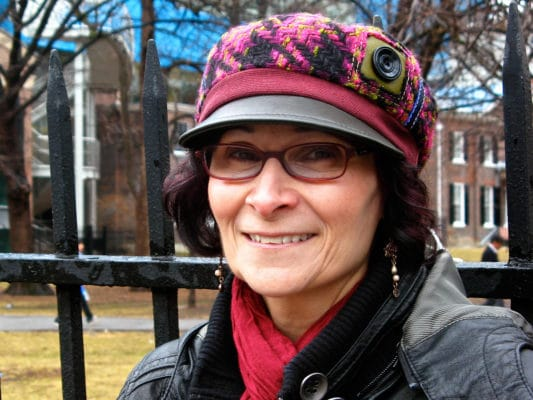 Woman with hot pink wool peaked cap on outside