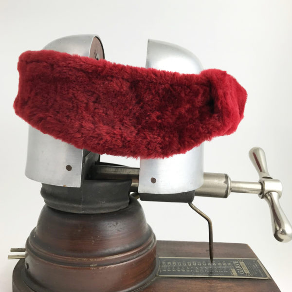 Side view of a Red Alpine Lamb Shearling Head Band against a white background