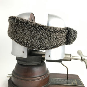 Side view of a snow top black Alpine Lamb Shearling Head Band against a white background