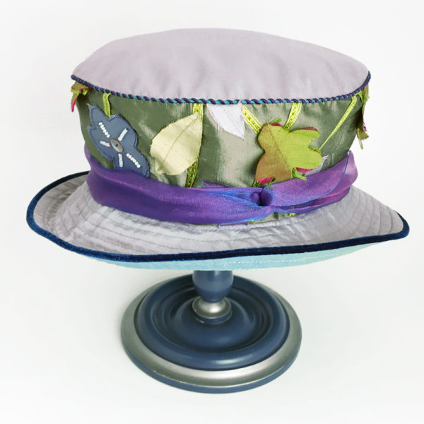 Side view of a green appliqué 100% silk Garden Tea Hat against a white background