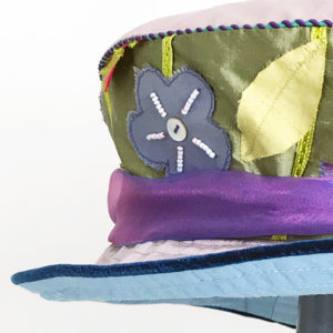 Close up view of a green appliqué 100% silk Garden Tea Summer Hat against a white background