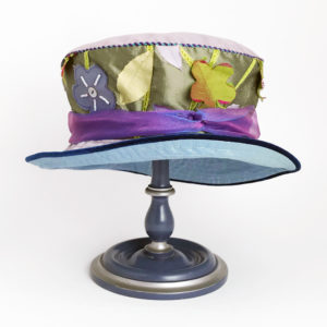 Front view of a green appliqué 100% silk Garden Tea Hat against a white background