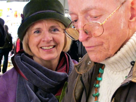 Woman wearing her LaBijou olive hat with a velvet silk scarf on behind her husband