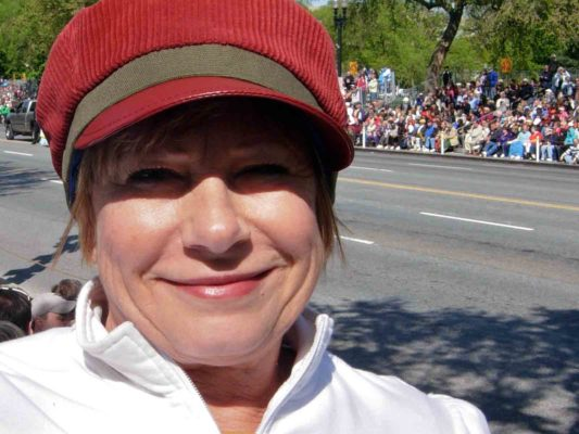 Close up of a woman smiling with a red Cordy Cap on.