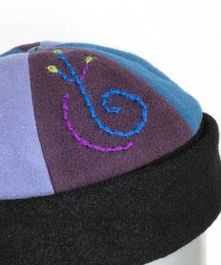 Close view of embroidery on blue and mauve Bean Toque against a white background