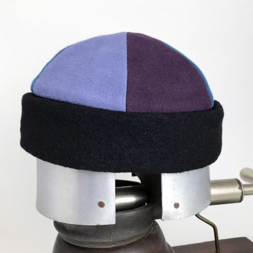 Side view of a blue and mauve of the Bean Toque against a white background