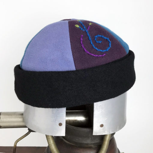 Side view of a blue and mauve showing the embroidery of the Bean Toque against a white background