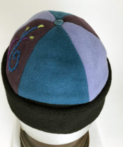 Top view of a blue and mauve Bean Toque against a white background