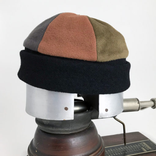 Side view of a earth tone coloured Bean Toque against a white background