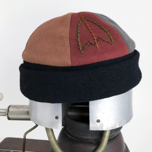 Side view of a earth tone coloured showing the embroidery of the Bean Toque against a white background