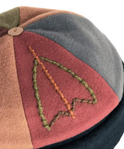 Close view of embroidery on the earth tone coloured Bean Toque against a white background
