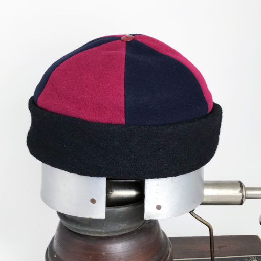 Side view of a red and black Bean Toque against a white background