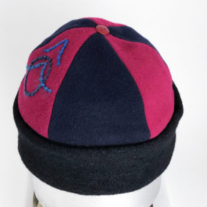 Top view of a red and black Bean Toque against a white background