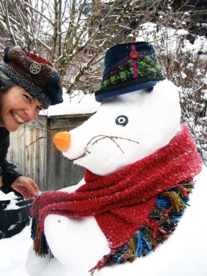 Gwendolyne tying a scarf around the neck of a Snow Rat wearing a Estonian hat.