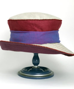 Front view of a crimson red and natural 100% linen Zinnia Summer Hat against a white background