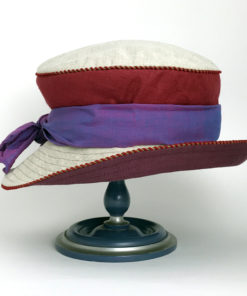 Side view of a crimson red and natural 100% linen Zinnia Summer Hat against a white background