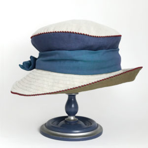 Side view of a denim olive and natural 100% linen Zinnia Summer Hat against a white background