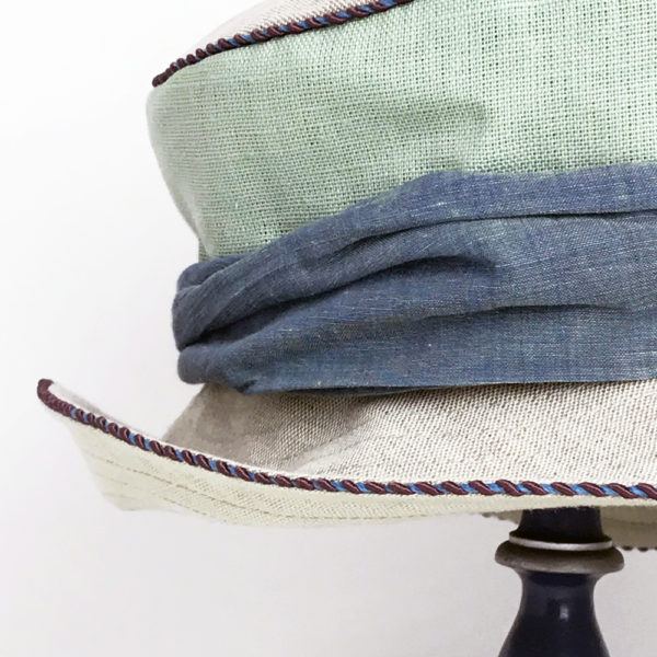 Close up view of a mint green and natural 100% linen Zinnia Summer Hat against a white background