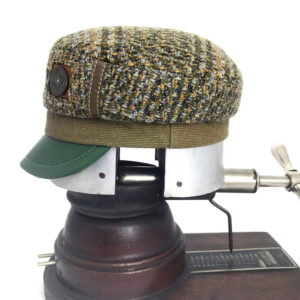 Side view of a olive green Abbey Road cap showing the button accent side against a white background