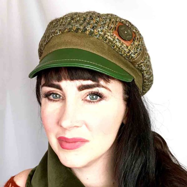 Close up view of a woman wearing olive green Abbey Road cap against a white background