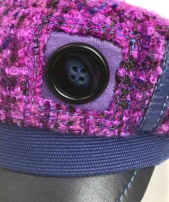 Close up detail button view of a purple boucle wool Abbey Road cap against a white background