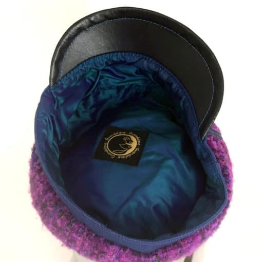 Inside view of a purple boucle wool Abbey Road cap against a white background