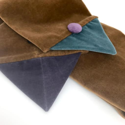 Detail of the seafood and mauve triangle ends on the beige Velvet Triangle Scarf made from 100% cotton velvet against a white background