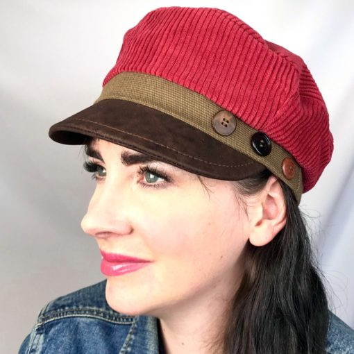 Close up view of a woman wearing red and brown Cordy cap against a white background