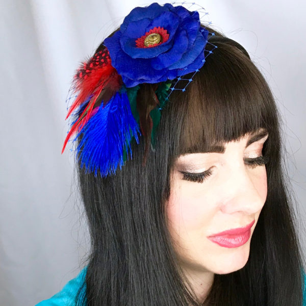 A close up of a woman wearing a dark blue red feather hair clip fascinator in her hair