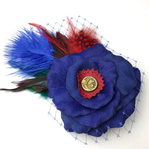 Front side of a dark blue red feather hair clip fascinator against a white background