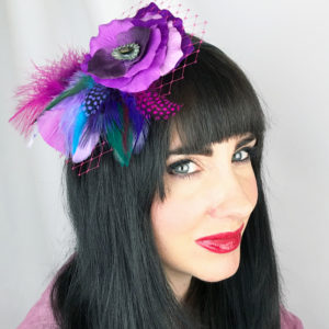 A close up of a woman wearing a fuchsia purple rose feather hair clip fascinator in her hair