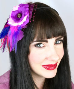 A close up of a woman wearing a fuchsia purple and pink rose and feather hair clip fascinator in her hair