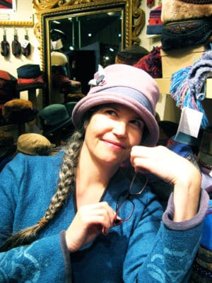 Gwendolyne with a pink Corona wool hat on smiling at in her booth at the winter OOAK show in Toronto