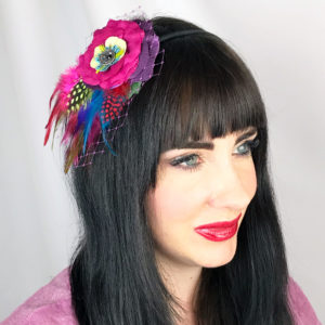 A close up of a woman wearing a hot pink rose feather hair clip fascinator in her hair